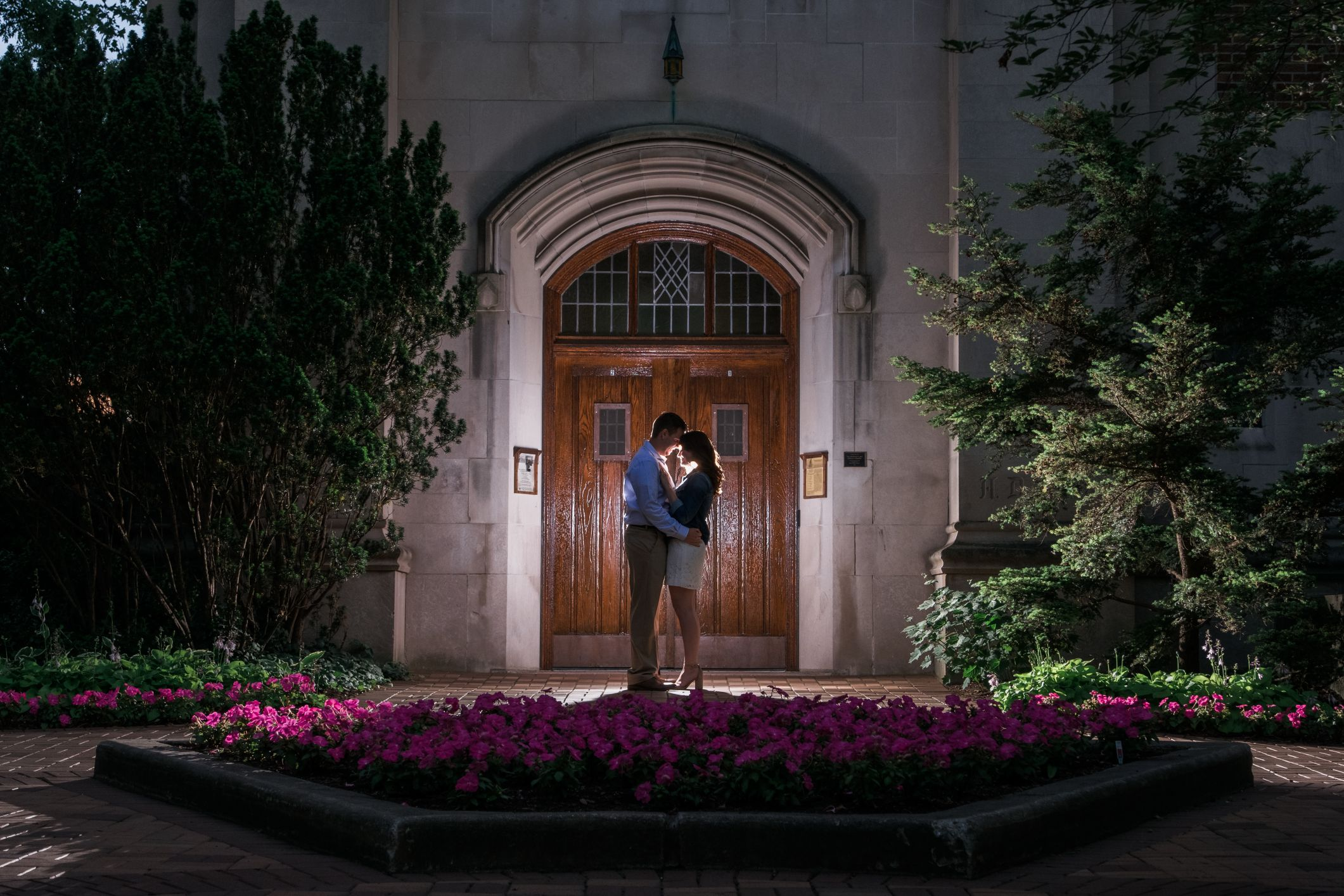 engaged couple at evening by wooden doors