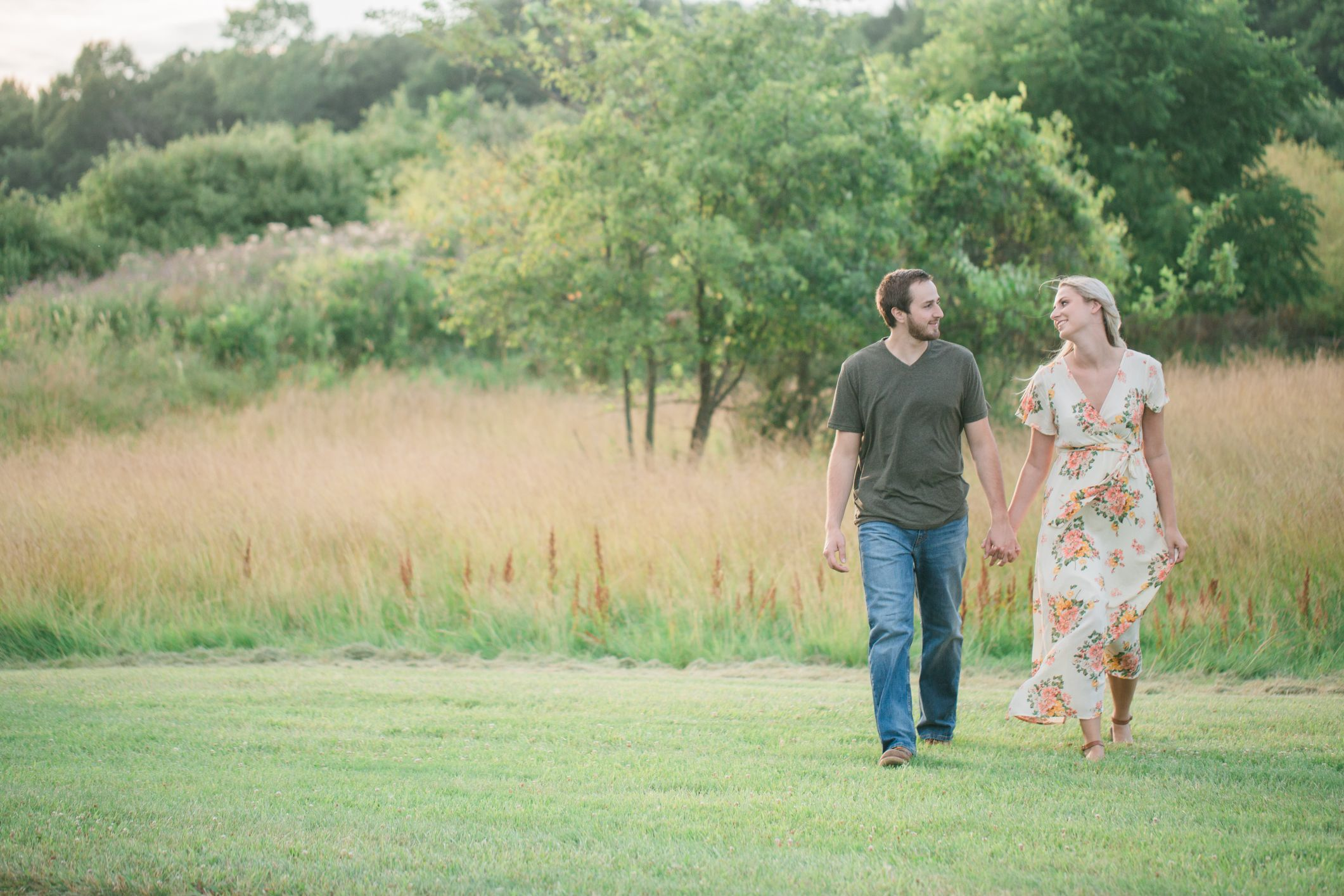 engaged couple walking in grass