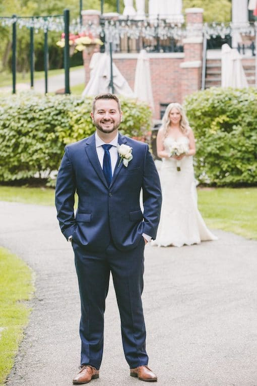 first-look-with-groom-in-focus-and-bride-approaching
