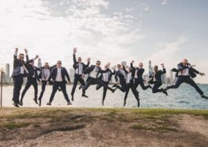 groomsmen jumping in air in front of detroit riverfrontjpg