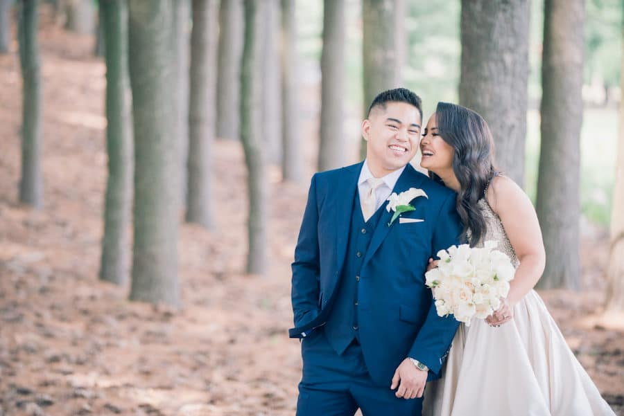 laughing bride and groom in the woods