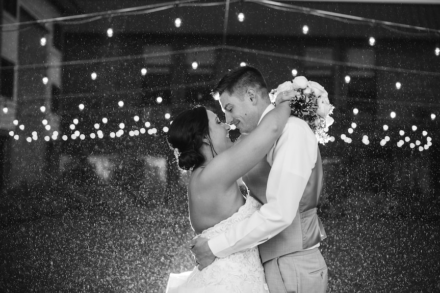 bride and groom first dance raining