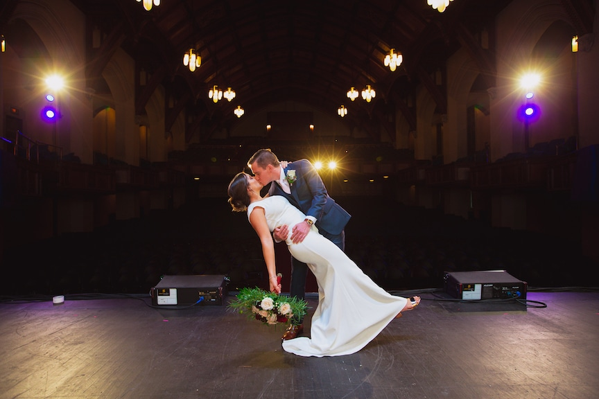 bride and groom kissing on stage
