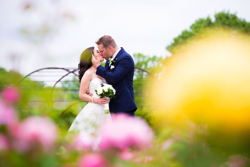bride and groom kissing with flowers