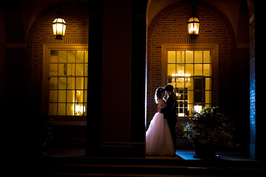 bride and groom outside brick wall evening