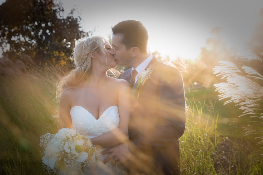 sunlight over bride and groom outside