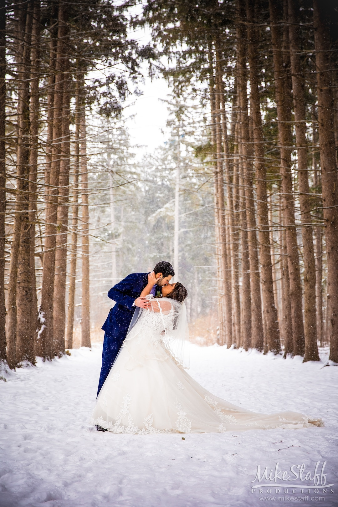 groom kissing bride outside in snow and woods