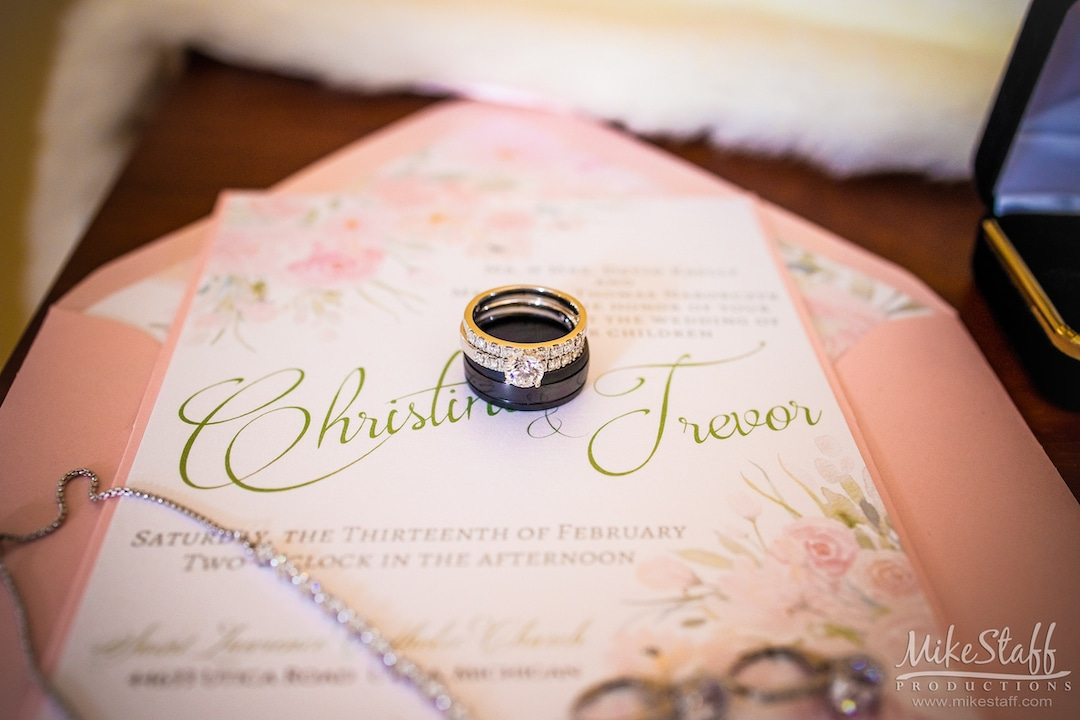 wedding rings on blush pink invitations