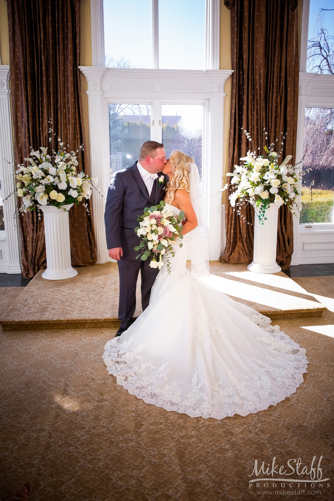bride & groom kissing at altar