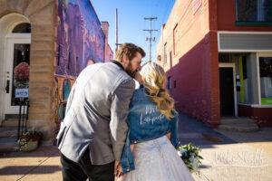 bride and groom jean jacket kissing